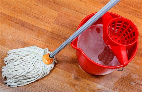 cleaning of wet floors by mop and red bucket with washing ...